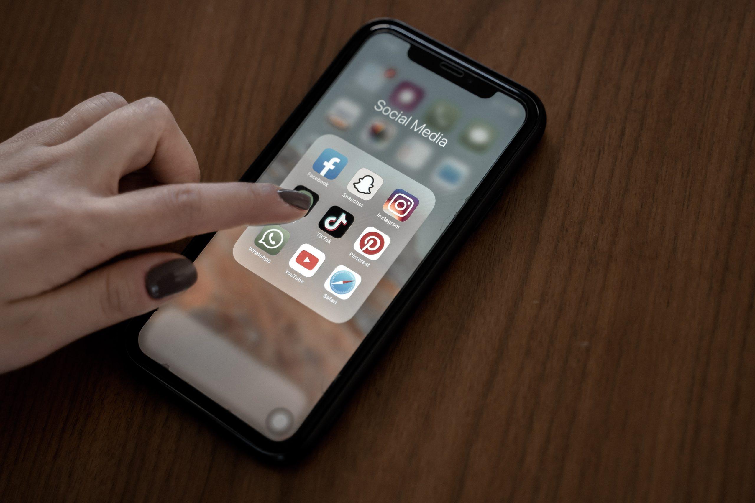 TikTok wordt aangeklikt op een telefoon waar meerdere social media platforms op te zien zijn.