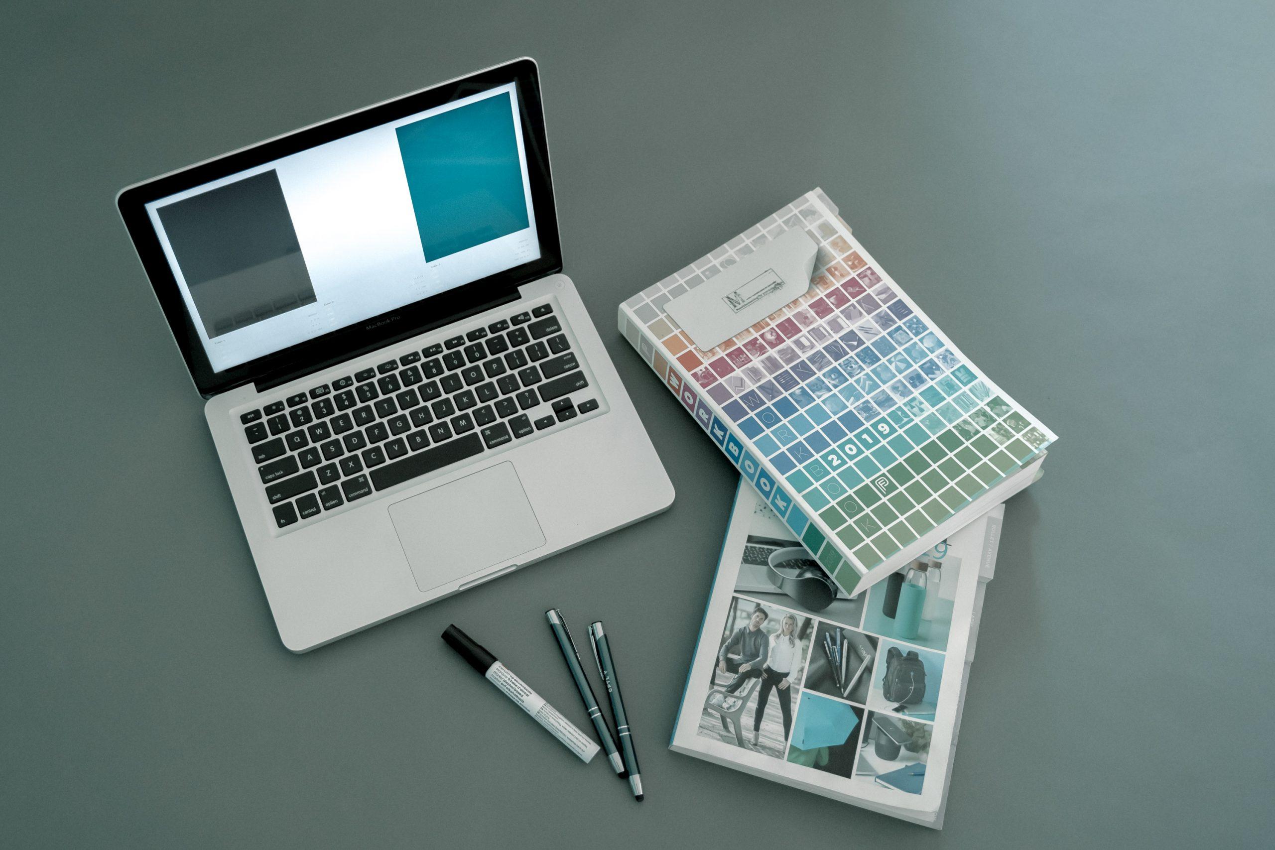 Laptop en boeken om te brainstormen over een huistijl. Bij een blog over branding en corporate identity.